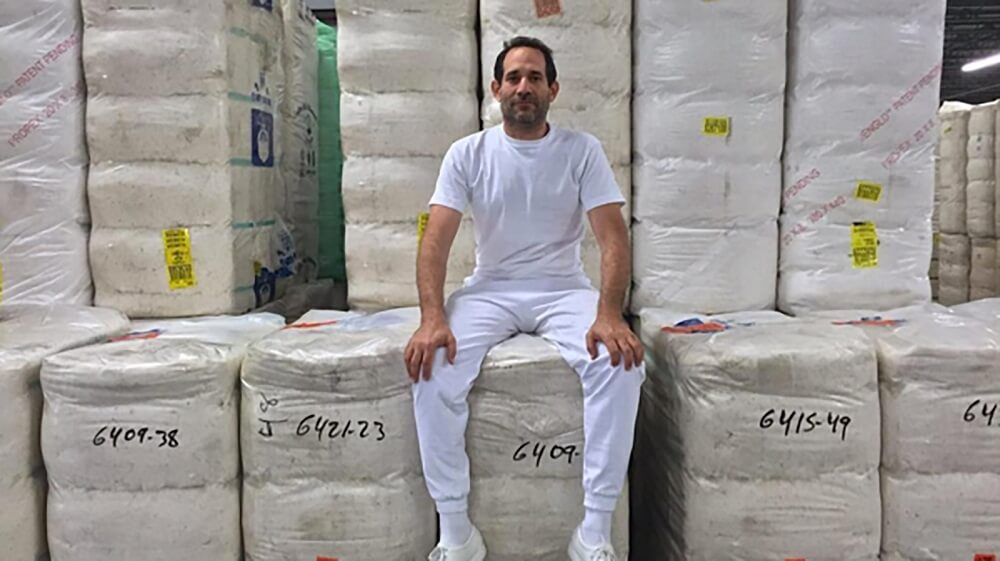 Dov Charney sitting proudly amongst his most recent project
